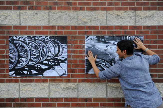 LITTLETON, CO - MAY 1: Angela Faris Belt smooths out a photograph after it was wheat pasted on a wall at the Arapahoe Community College Art & Design Center in Littleton, Colorado on May 1, 2015. Littleton is the latest metro community to launch a First Friday Art Walk, taking place in downtown Littleton the first Friday of every month. (Photo by Seth McConnell/The Denver Post)